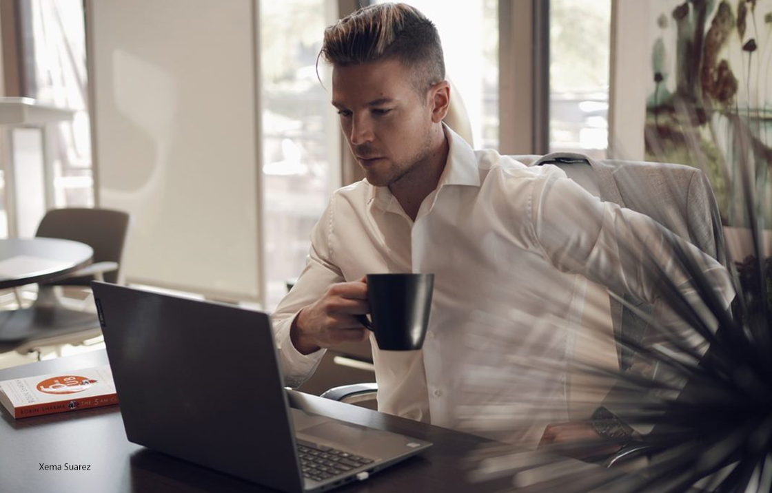 Man sitting at desk with coffee and laptop