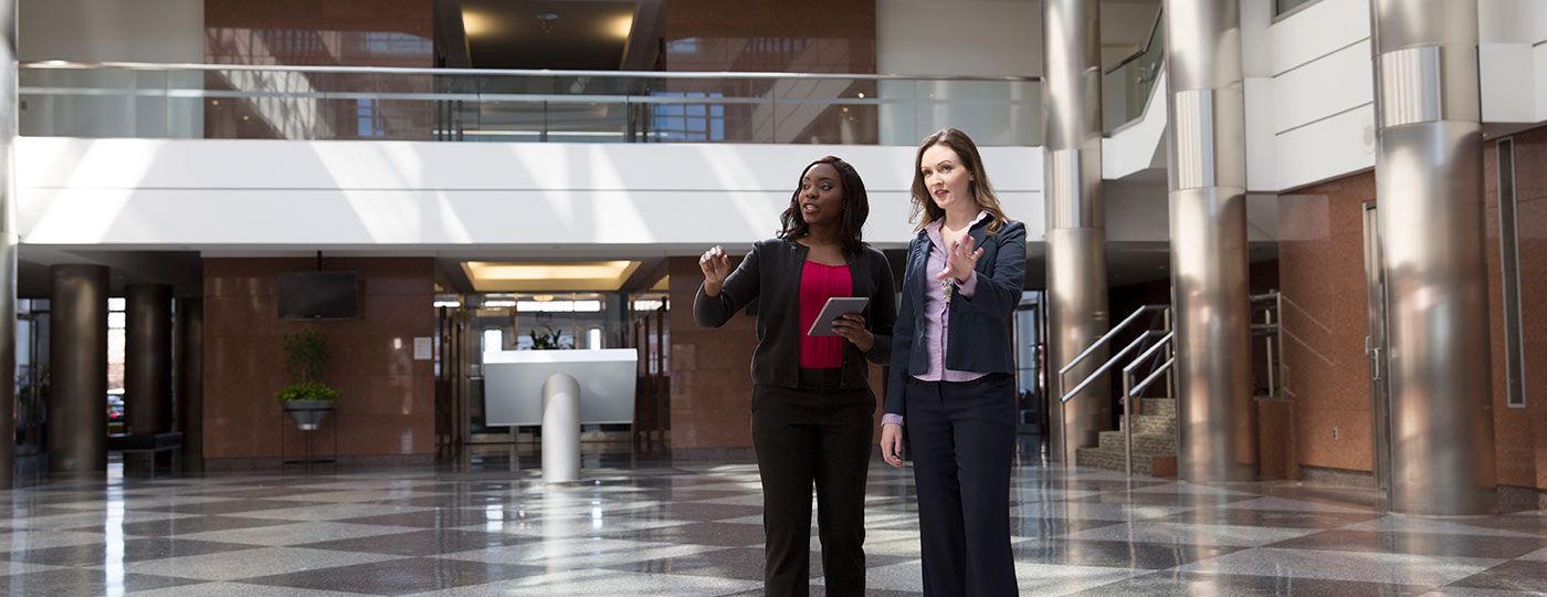 Two women in professional suits standing in a tiled office building lobby