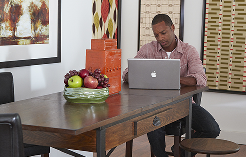 Man at computer in his dining room