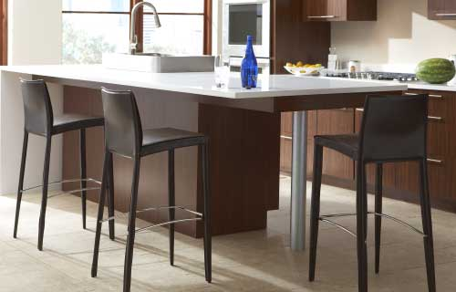 CORT black counterheight Glide barstools in a kitchen with white countertops and wood cabinets