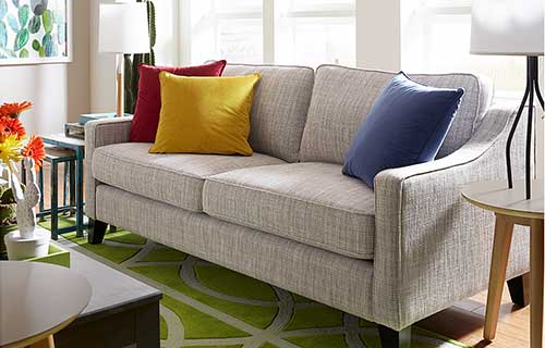 Gray Hensley sofa with blue, yellow and red spectrum pillows