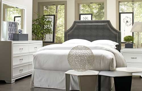Fabric upholstered headboard in bedroom with matching white wooden dresser and nightstand