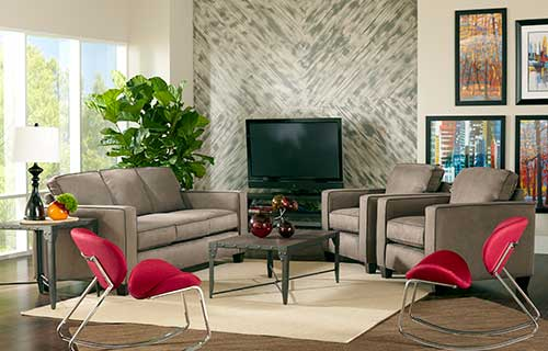 Neutral color Austin sofa with two red accent chairs arranged on a beige area rug in front of a large window