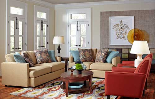 Sander sofa and loveseat with colorful accent pillows and Beaumont wooden coffee table by CORT in a sunny living room