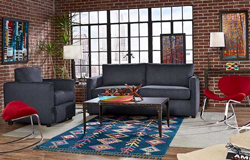 Blue Levi sofa and Levi accent chair with the Kendrick coffee table in a living room with brick walls and a large window