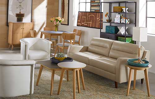 Danish Modern Isabel beige leather sofa with two white accent chairs and three Hendrick accent tables in a sunny living room