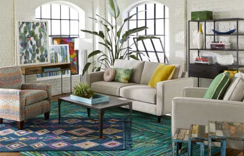 Addison sofa and accent chair with Mackenzie coffee table by CORT in living room with white brick walls and blue area rugs