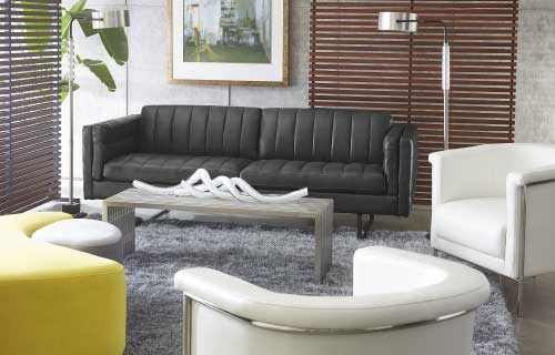 Black leather Baldwin sofa with white Bianca accent chairs in a living room with a gray area rug