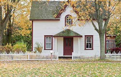 White house with red trim and a white picket fence on an autumn day