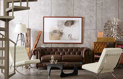 Brown leather Emerson Chesterfield sofa with two white accent chairs and a Marco glass coffee table