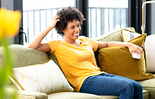 Person on couch wearing yellow tshirt holding phone