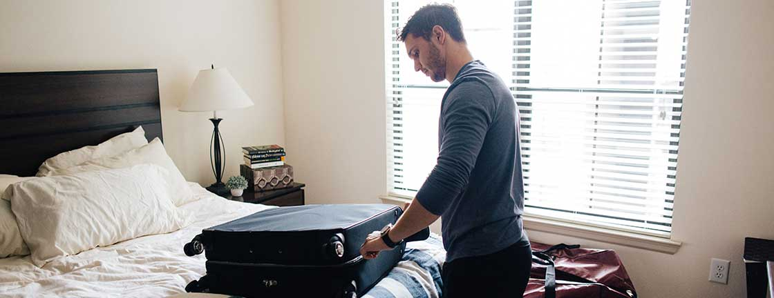 Man packing suitcase in bedroom