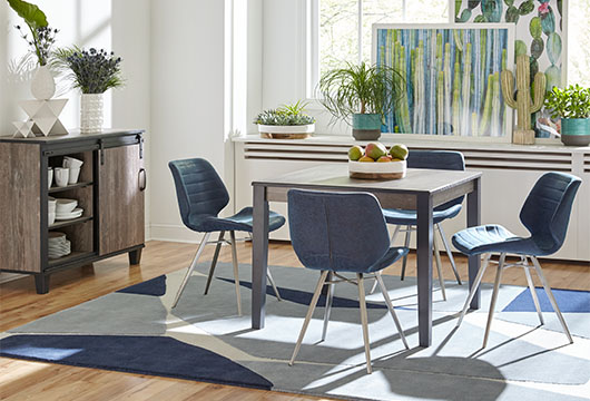 Brown wood Smores dining table with blue Giada chairs by CORT in brightly lit dining room with blue geometric area rug