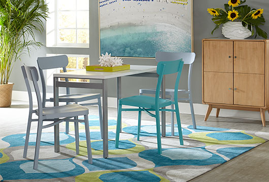 Four blue and gray Boardwalk dining chairs around a white table in a bright room with a blue and green area rug