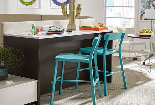 Two blue Boardwalk stools at a white countertop in a sunny office space