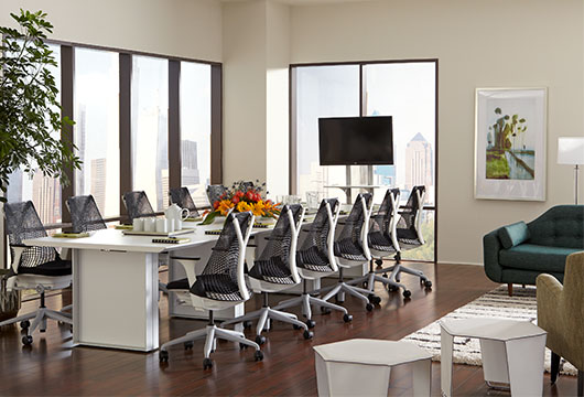 Quorum white conference table by CORT surrounded by black office chairs in a large room with windows