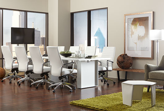 White leather office chairs around a white conference table with office buildings visible in the window