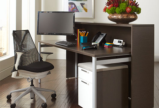 The Nex dark chocolate reception counter with an office chair in a lobby in front of an open window