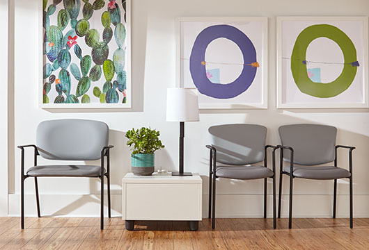 Three gray waiting room chairs against a white wall with colorful artwork in an office lobby