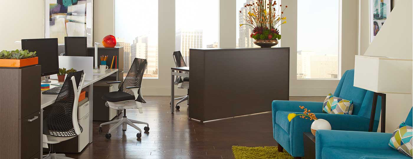 Lobby area in office with large window furnished with Staks desks and Nex reception desk by CORT