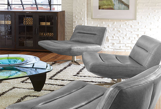 Three gray Mila accent swivel chairs in an office lounge area with a glass coffee table