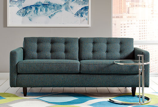 Blue-gray Darby sofa by CORT Furniture resting on blue and green area rug in front of a window on a sunny day
