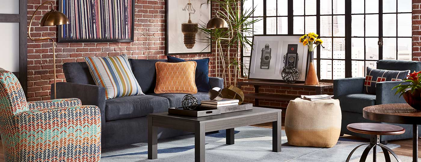 Blue Levi sofa with orange and blue accent chair and Dorain coffee table in loft-style living room
