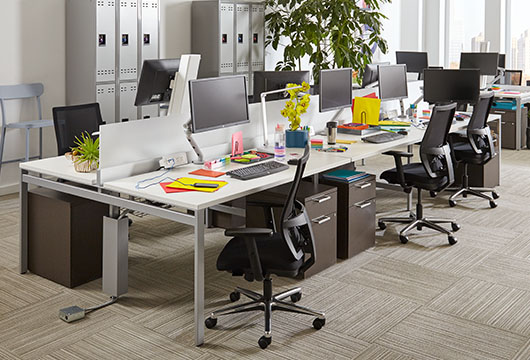 Staks benching tables with black office chairs in an open corporate office