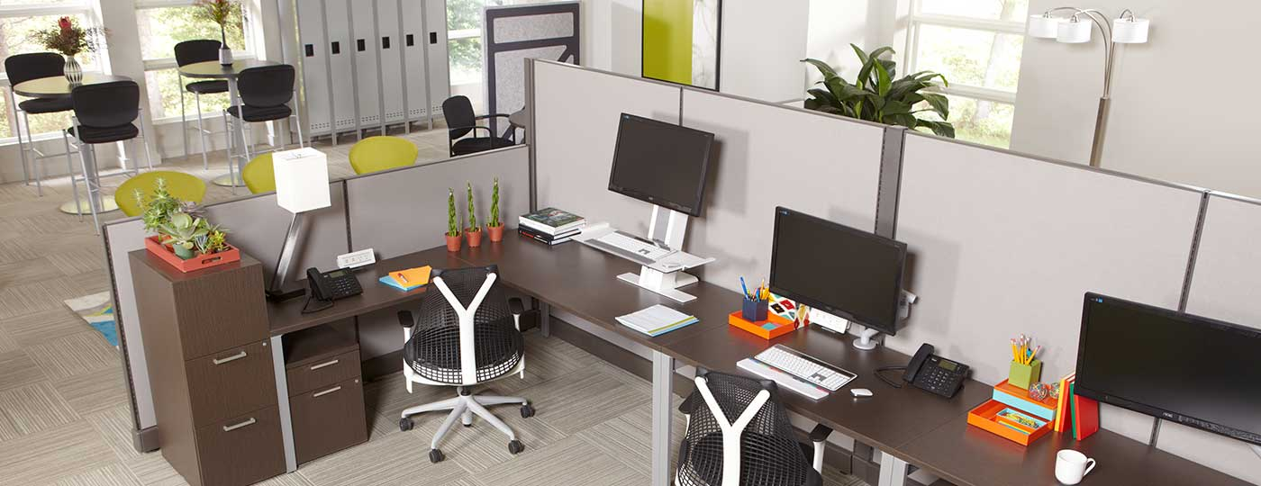 Staks white workstations with matching black and white Staks office chairs in a brightly lit workplace