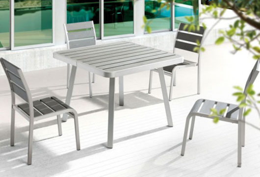 Metal Township table and chairs on an outdoor patio by CORT Furniture