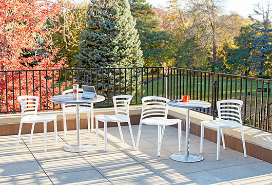 Silver-colored Entourage cafe table with white chairs by CORT on an outdoor patio on a sunny day with trees in the background