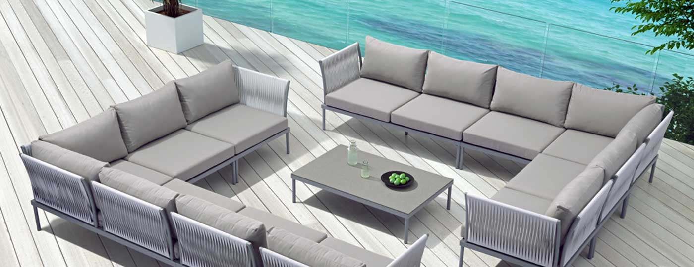 Two Sand Beach outdoor sofas in an outdoor seating area with a coffee table on a patio with the ocean in the background