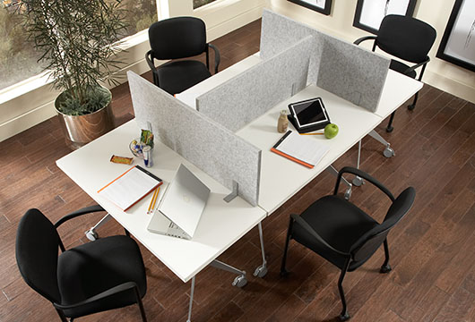 White Q training table pods with black desk chairs by CORT set up with divider desk screens in an office training room