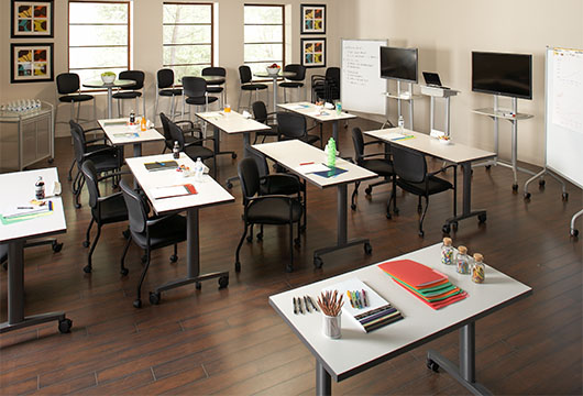 Eight tables arranged in a training room with a wooden floor facing two whiteboards and two televisions