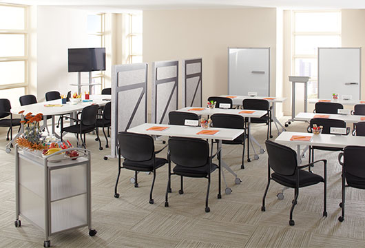 Brightly lit training room with seven white tables, black office chairs, and multiple rolling whiteboards