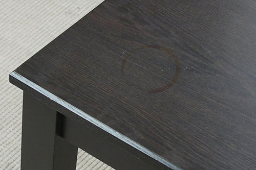 Bargain table with circular ring stain on top surface