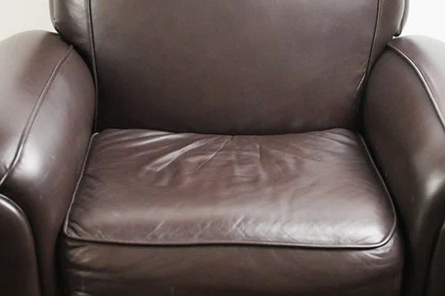 Used chair with worn and creased leather cushion