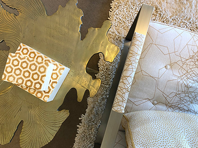 sode table with gold plate next to white chair with gold accents