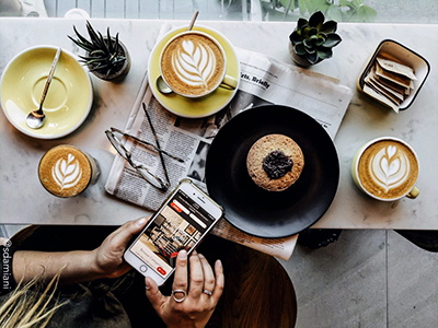 woman on a cell phone next to a bar table with a coffee and muffin on the table top