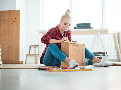 woman sitting on floor working on cabinet